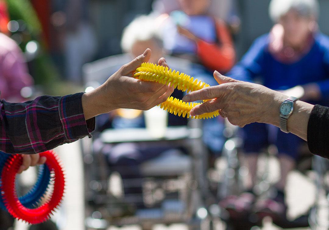 Zwei Menschen reichen sich über einen Spielring die Hand